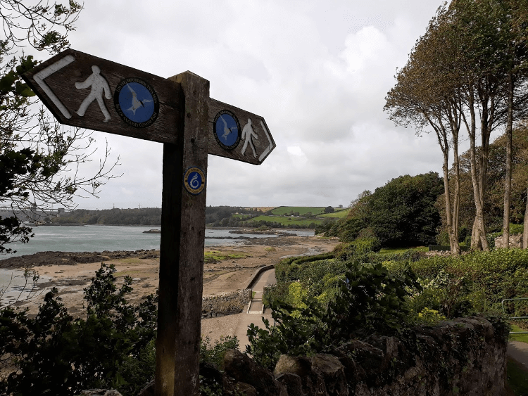 A signpost overlooking a sandy bay on the Anglesey Coast Path