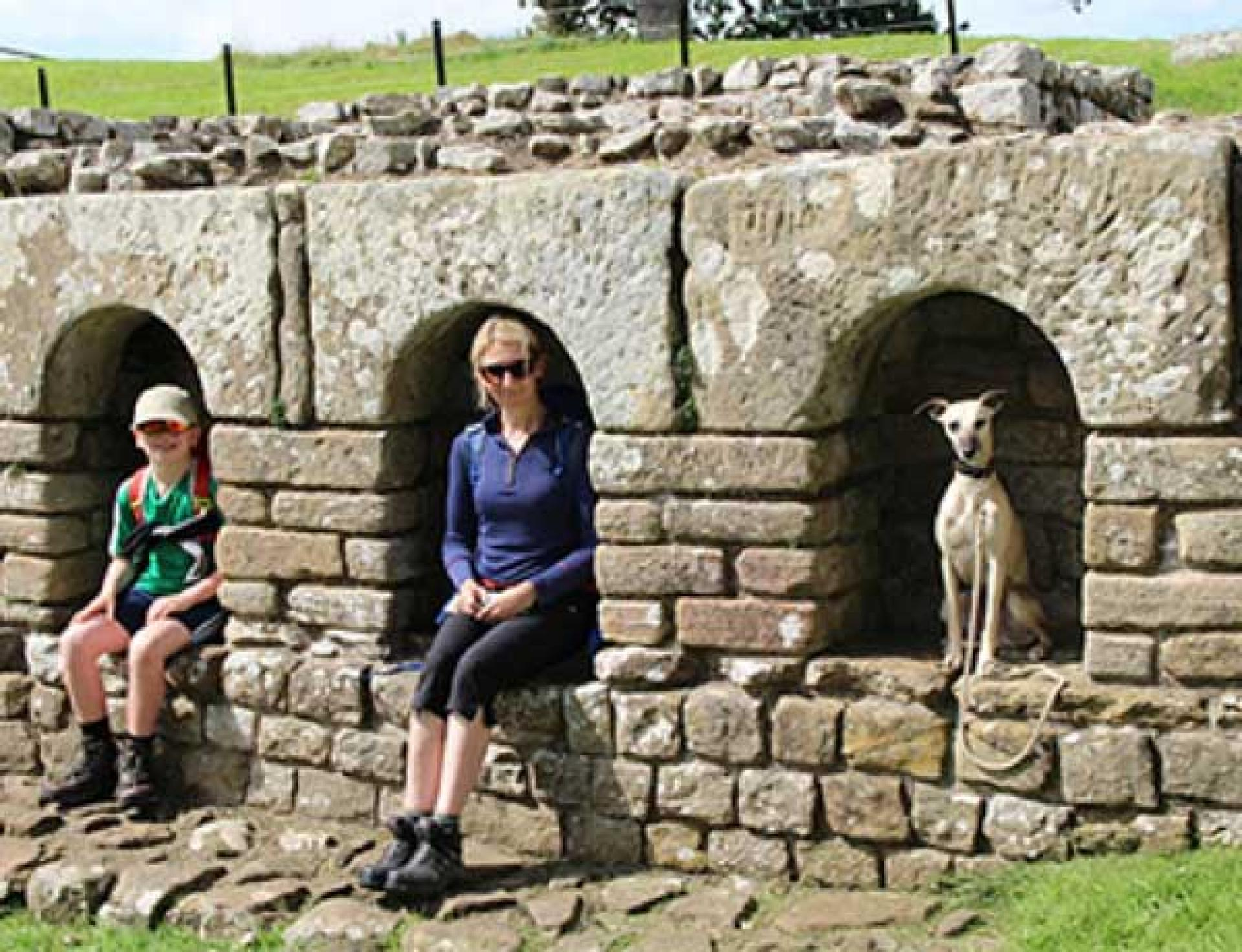 Dog and family sit in Roman ruins along Hadrian's Wall Path