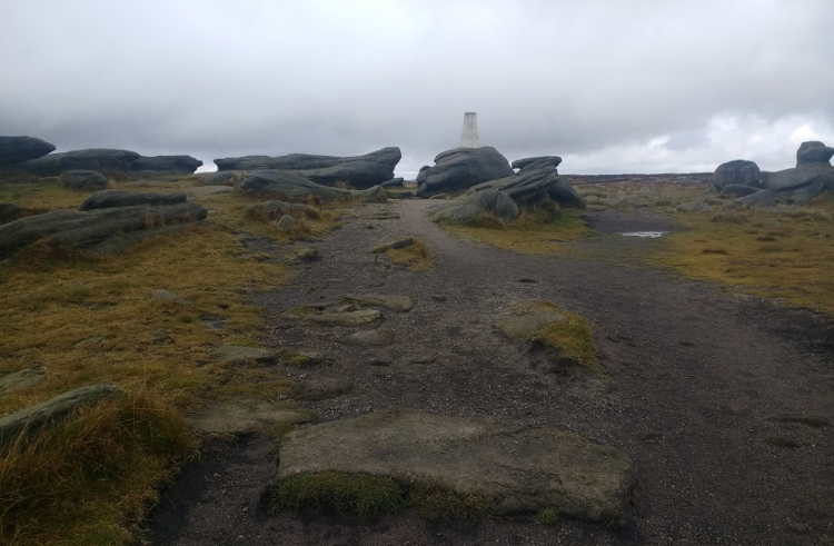 Looking up at a trig point across peaty land.