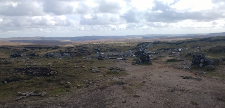Wreckage from the plane crash is scattered across an expanse of moorland.