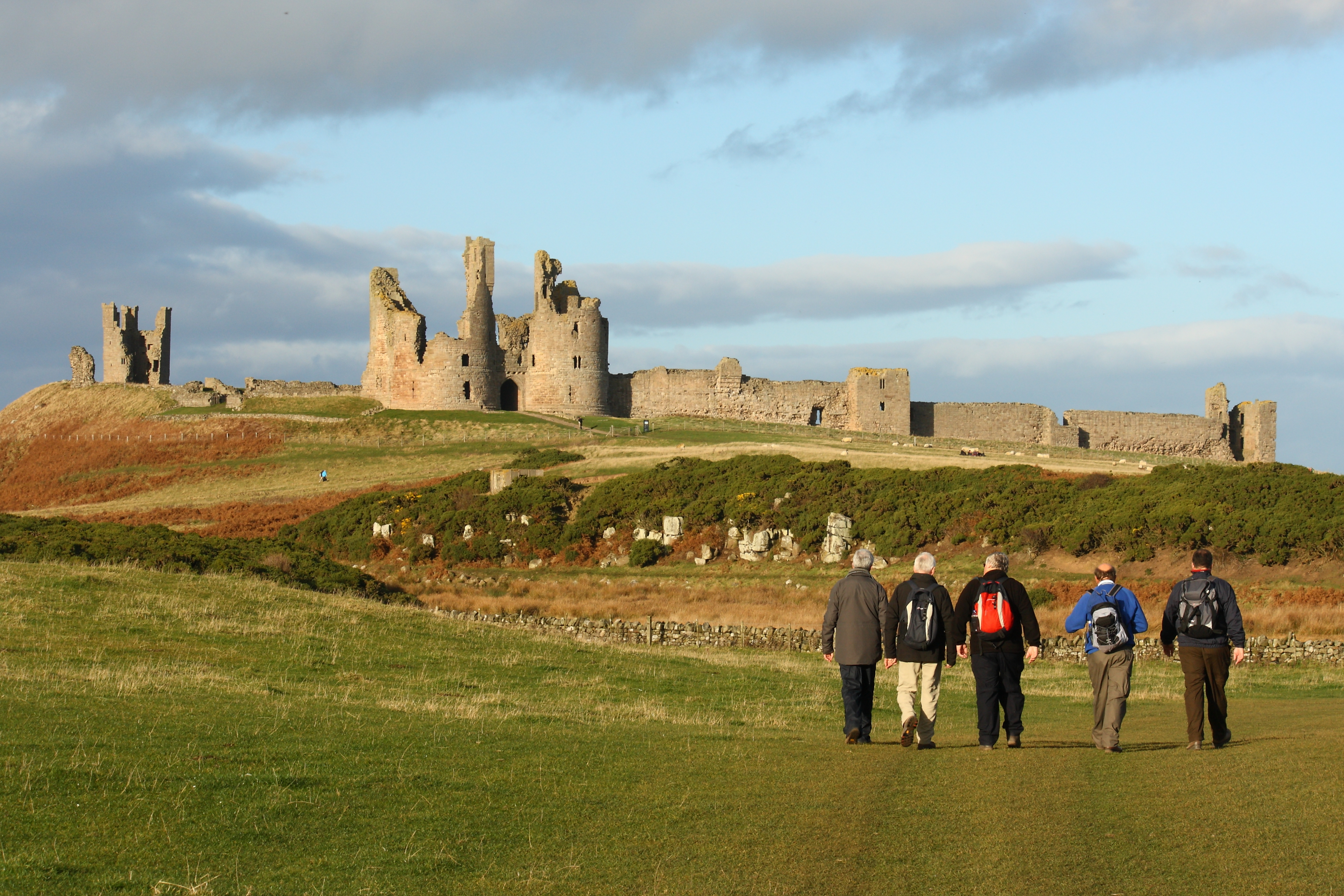 walkers at Dunstanburgh castle in Northumberland, UK