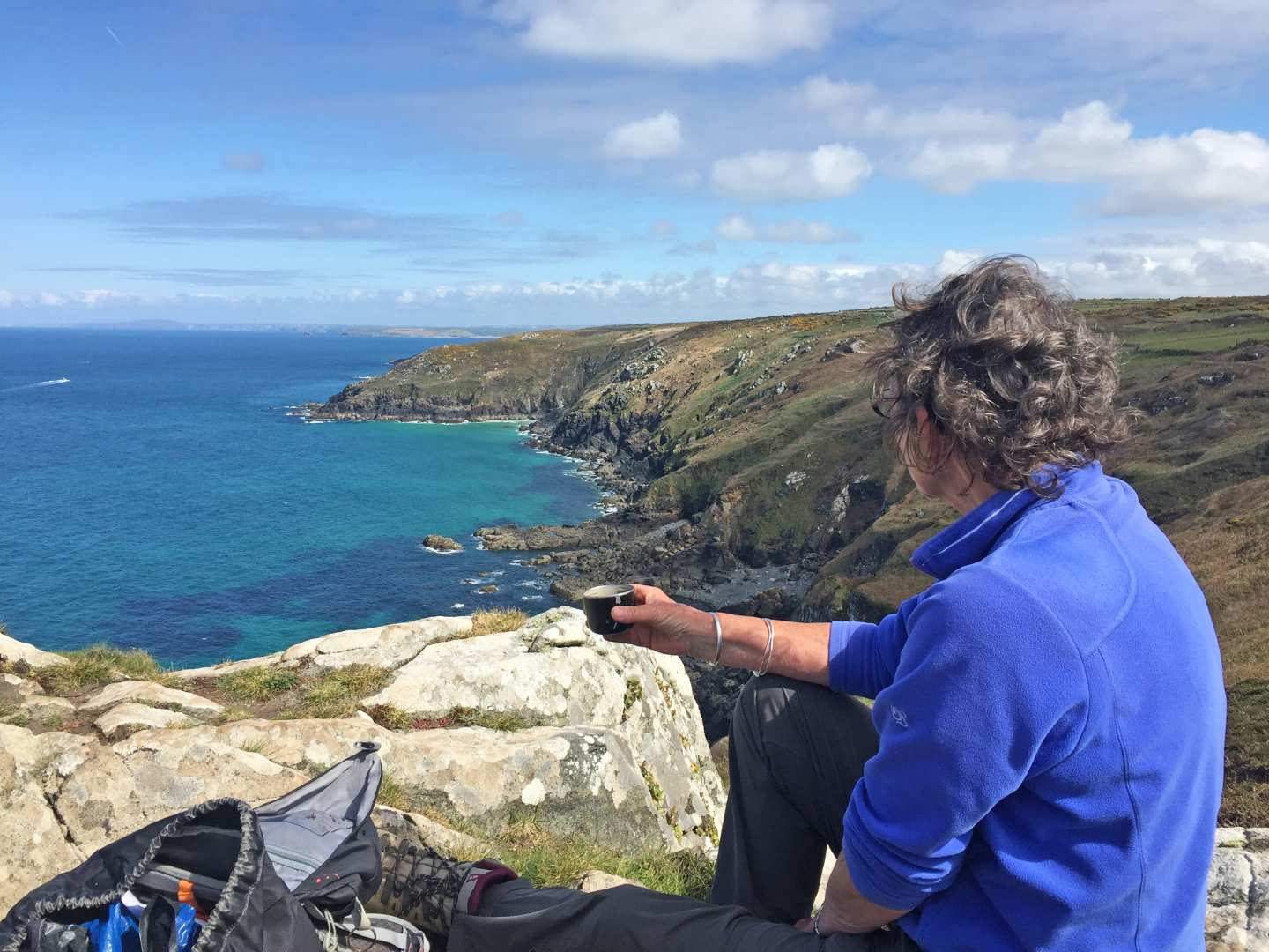 A walker sits on the Cornish coast with a cup of tea